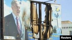 Жартылай жанып кеткен президент Нұрсұлтан Назарбаевтың бейнесі басылған банер. Жаңаөзен, 19 желтоқсан 2011 ж.