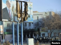 Вооруженные полицейские на улице Жанаозена рядом с поврежденным билбордом с изображением президента Нурсултана Назарбаева. 19 декабря 2011 года.