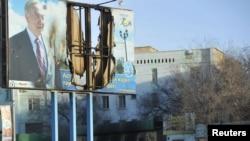 Қақтығыс кезінде жартылай жанып кеткен плакат. Жаңаөзен, 19 желтоқсан, 2011 жыл.