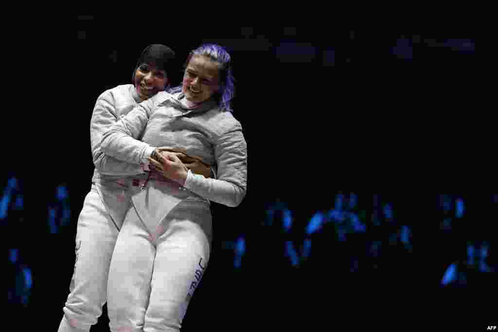 U.S. fencers Ibtihaj Muhammad (left) and Dagmara Wozniak celebrate after winning the women's team saber bronze medal bout with Italy.