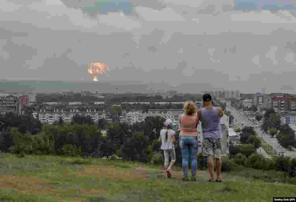 A family watches the explosions from afar.