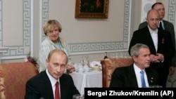 Уладзімер Пуцін з Джорджам Бушам на працоўнай вячэры ў Санкт-Пецярбургу пасьля саміту G8 19 ліпеня 2006 г. Яўген Прыгожын стаіць за Джорджам Бушам