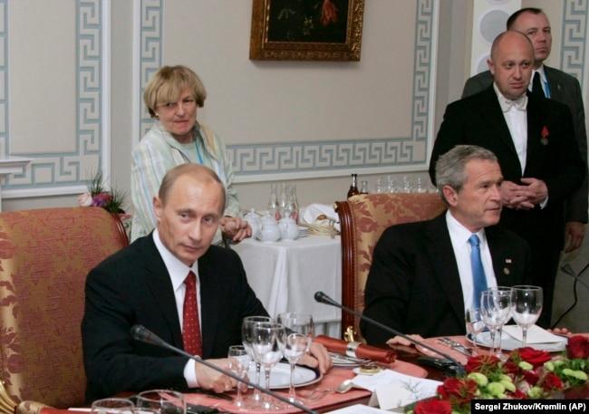 Владимир Путин с Джорджем Бушем на рабочем ужине в Санкт-Петербурге после саммита G8 19 июля 2006 г. Евгений Пригожин стоит за Джорджем Бушем.