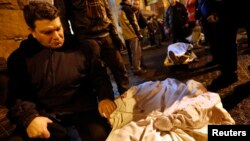 Мужчина у тела своего сына, убитого во время столкновений в Киеве. Фото сделано в холле киевской гостиницы, где врачи-добровольцы развернули госпиталь для раненых демонстрантов. 20 февраля 2014 года.