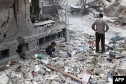 A Syrian boy collects items amid the rubble of destroyed buildings following reported air strikes in the rebel-held town of Douma, on the eastern outskirts of the capital, Damascus, on October 3.
