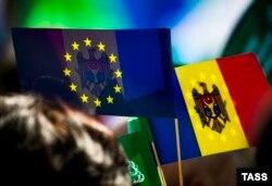 Флажки Молдавии и Евросоюза в руках участников митинга в Кишиневе