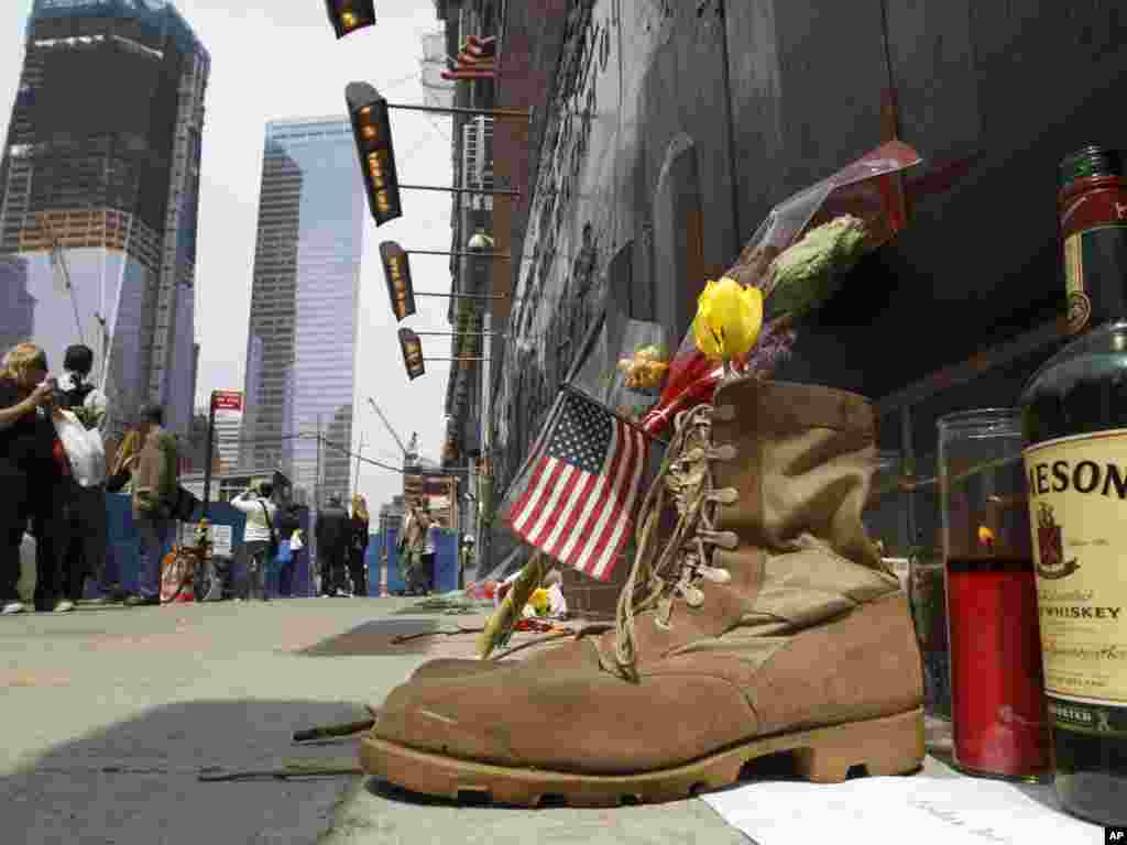 A pair of military boots, a bottle of whisky, and a memorial candle are placed at the base of a 9-11 memorial across the street from Ground Zero in New York, one day after bin Laden was killed. Photo by Kathy Willens for AP.
