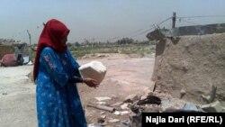سيدة عراقية تخبز في تنور من الطين