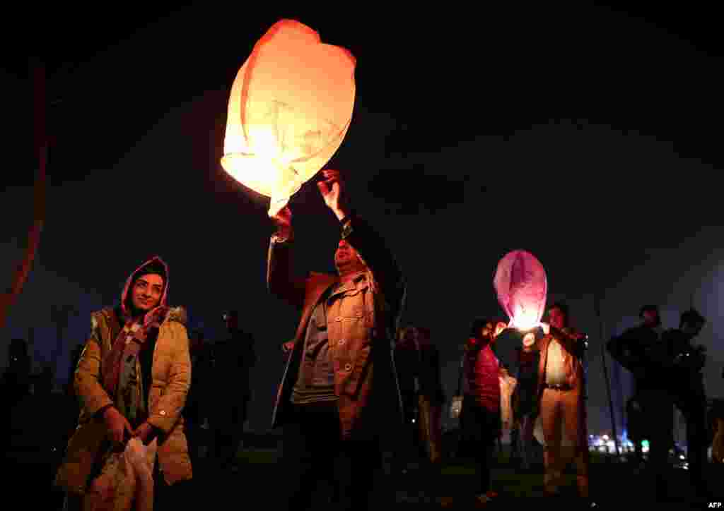 Iranian families release lanterns in a park in Tehran on March 17. (AFP/Behrouz Mehri)