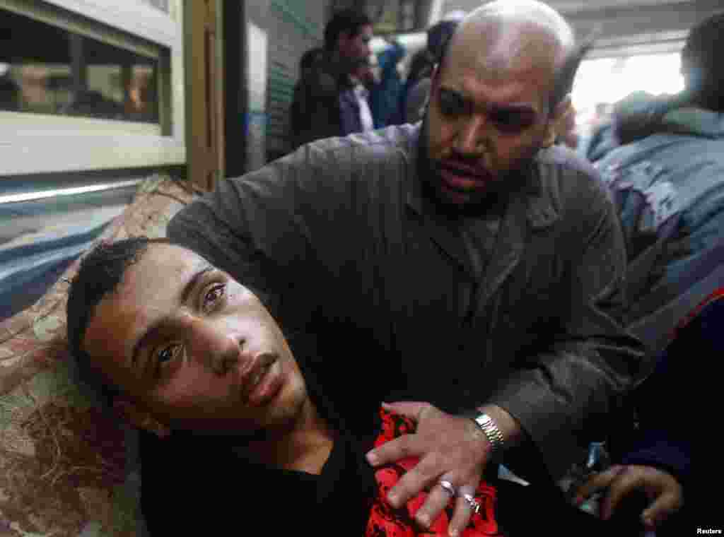 A protester attends to an injured man during clashes in Cairo on January 28, 2011.
