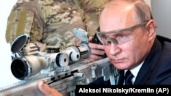 Russian President Vladimir Putin aims a sniper rifle during a visit to a military exhibition center outside Moscow on September 19.