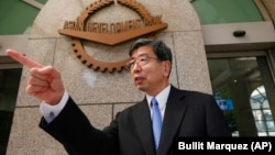 Philippines -- Asian Development Bank President Takehiko Nakao gestures to an aide outside the financial institution's headquarters near Manila, January 8, 2016.