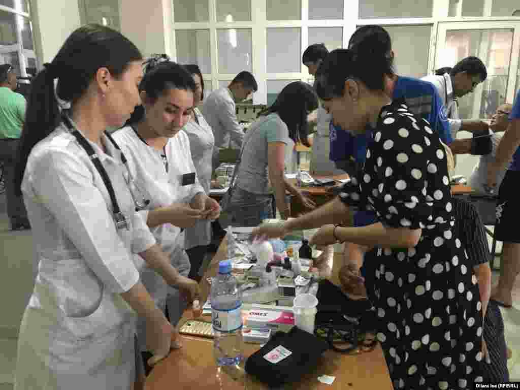 Медицинские работники во время обследования людей, эвакуированных из города Арысь.