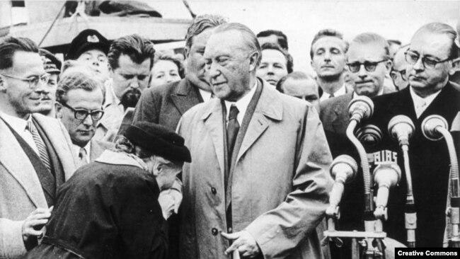 Мать немецкого военнопленного целует руку Аденауэра, 1955 год