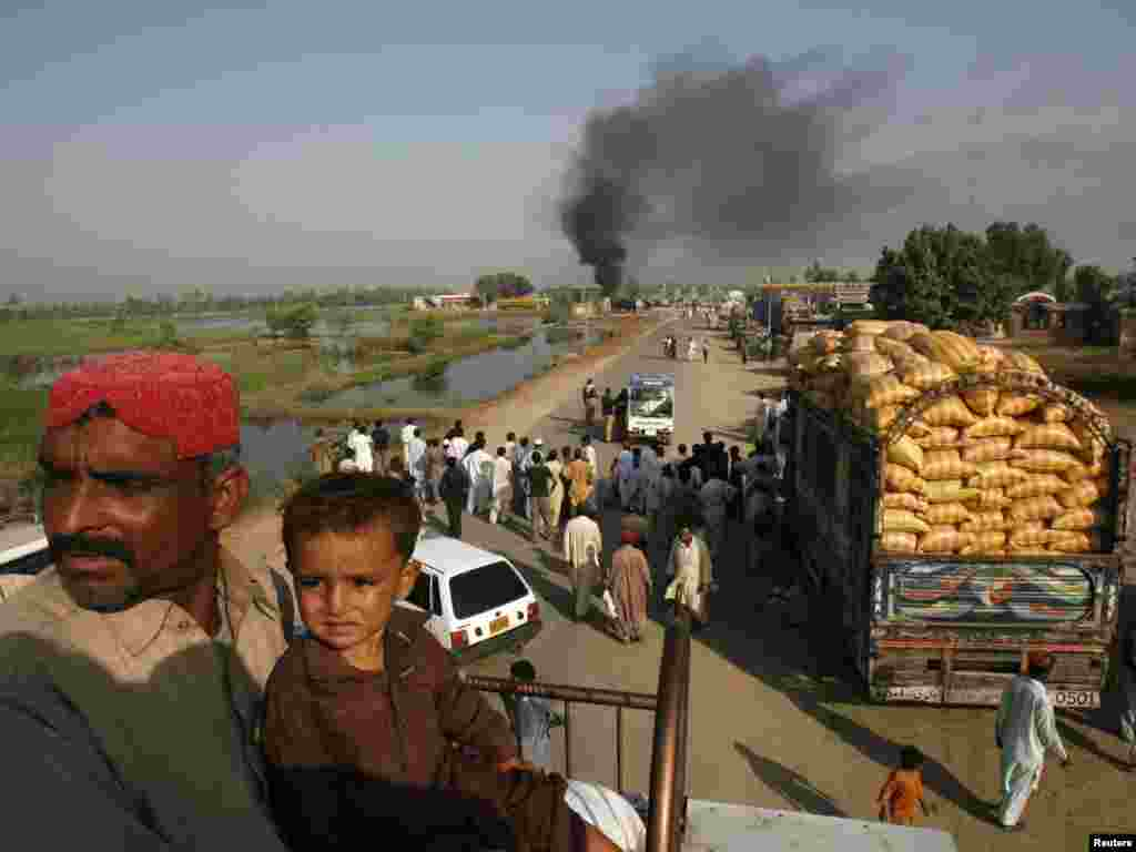 "Passengers sit on the roof of a bus near oil tankers burning after ""suspected militants"" set fire to them on a highway near Shikarpur, in Pakistan's Sindh Province, on October 1. One day earlier, three Pakistani troops had been killed in a cross-border NATO air strike. Photo by Athar Hussain for Reuters"