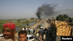 Passengers sit on the roof of a bus near burning oil tankers on a highway near Shikarpur, Pakistan, on October 1.