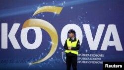 Un poliţist kosovar în faţa unui poster la Priştina la aniversarea a 5-a a proclamării independenţei Kosovo faţă de Serbia, 17 februarie 2013