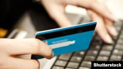 Czech republic. Internet shopping. Hands entering credit card information into a laptop. Shutterstock.