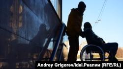 Мужчина в кресле-коляске и его сопровождающий.