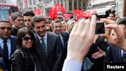 Turkey -- Main opposition Republican People's Party (CHP) mayoral candidate Mustafa Sarigul (3rd L) poses with a woman for a souvenir picture as he walks in the main Istiklal street as part of his election campaign in Istanbul, March 27, 2014