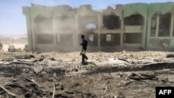 An Afghan policeman inspects the site of a suicide attack in Zabul on May 25.