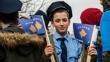 A young Kosovar boy dressed as a police officer holds Kosovar flags on the eve of the celebrations marking the 10th anniversary of Kosovo's independence, in Pristina on February 16.