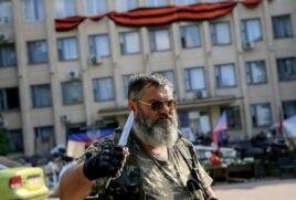 Пророссийский активист с ножом стоит у здания местной администрации. Краматорск, 7 июня 2014 года.