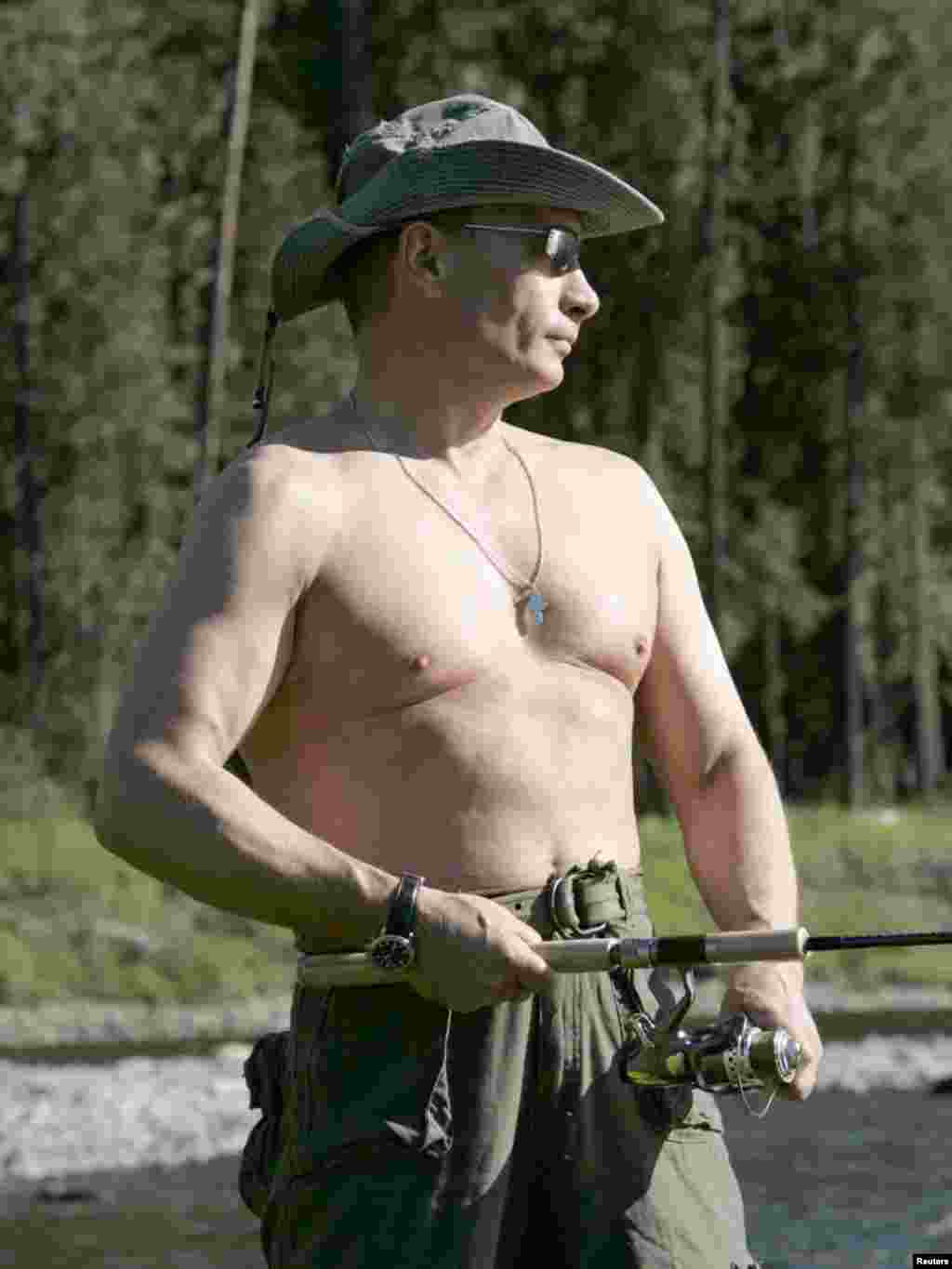 Russia's President Vladimir Putin fishes in the Yenisei River in Siberia as he makes a tour together with Prince Albert II of Monaco, August 13, 2007. REUTERS/RIA Novosti/KREMLIN