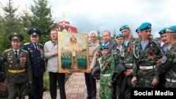 Военнослужащие с картиной, написанной под икону, где изображен Сталин в виде святого