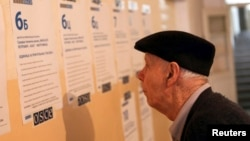 A man reads balloting instructions at a polling station in Kosovo's ethnically divided town of Mitrovica before casting his vote in the Serbian elections on March 16.