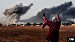 A woman reacts as smoke rises from the Syrian town of Kobani on October 13 after a strike from the U.S.-led coalition that is targeting the Islamic State militants besieging the town, seen from the Turkish-Syrian border.