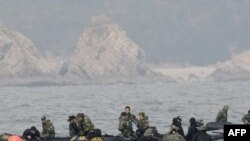 "South Korean navy personnel search for survivors and bodies from the sunken ""Cheonan"" near the border with North Korea in late March."