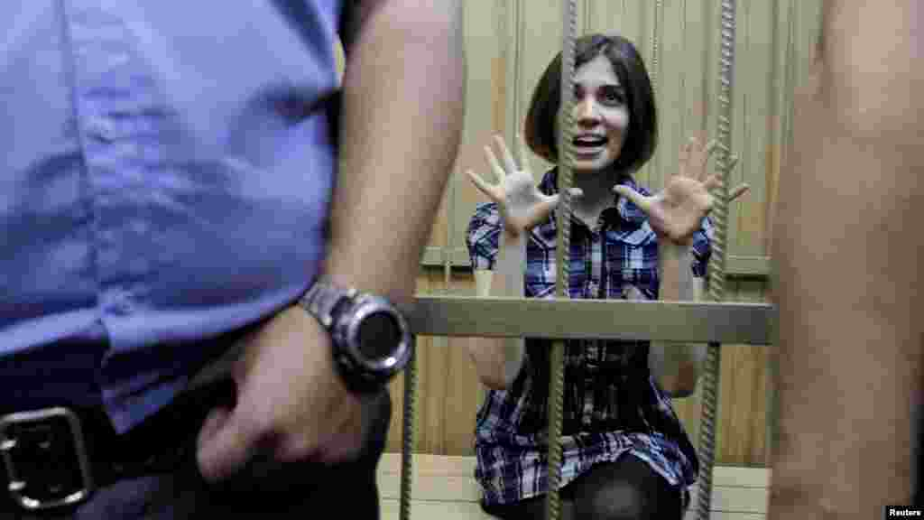 Nadezhda Tolokonnikova, a member of the female punk band Pussy Riot, which is accused of hooliganism, gestures as she sits behind bars during a court hearing in Moscow. (Reuters/Denis Sinyakov)
