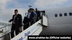 """Футболисты карагандинской команды """"Шахтер"""" спускаются с трапа самолета в Глазго."""