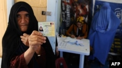 An elderly woman displays her identification card to vote in Afghanistan's forthcoming presidential election at a registration center in Herat.