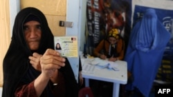 هرات: یوه زړه ښځه د ولسمشرۍ راتلونکو ټاکنو کې د خپلې رای اچولو لپاره خپله پېژندپاڼه ښيي، چې نوم ولیکي.