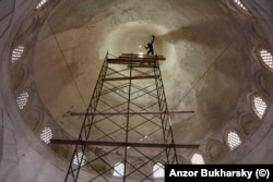 A worker clings to a safety rope as he plasters the roof of a mosque.