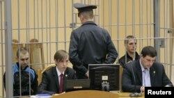 Обвинетите Димитри Канавалау и Владислав Кавалју се во кафез за време на судењето.