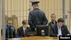 Dzmitry Kanavalau (left) and Uladzislau Kavalyou sit in a cage before court hearings in Minsk in September 2011.