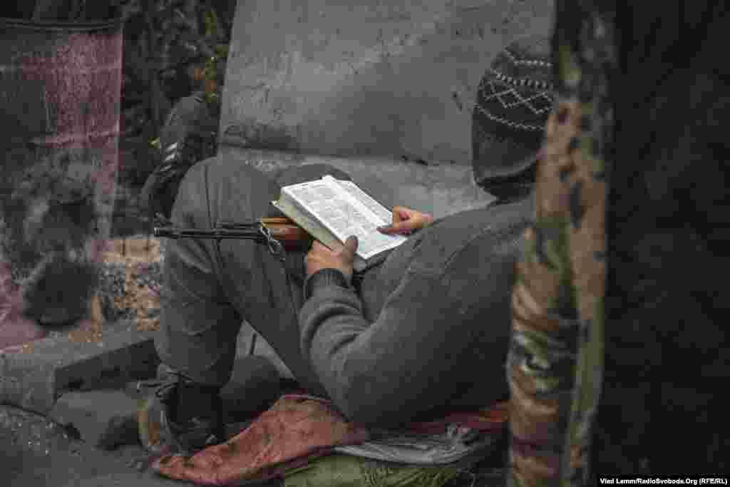 """Боец полка """"Днепр-1"""" читает Библию на своем блокпосту."""