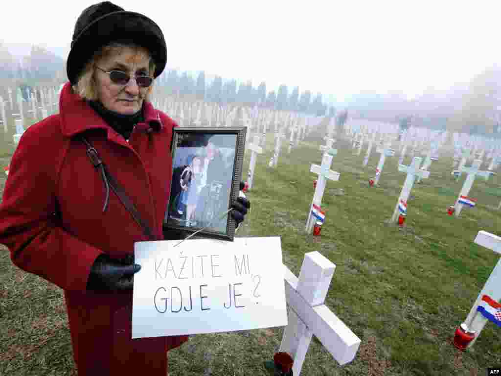 "Jelena Radic, 63, shows a picture of her disappeared husband and war victim Mijo as she holds a sign reading, ""Tell me where is he?"" at a 1991 war victims cemetery in Vukovar, Croatia, on November 18. (AFP PHOTO/Hrvoje Polan)"