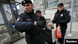 Russian police detain a protester against Russian President Vladimir Putin after she took part in a lone picket in central Moscow in April.