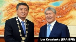 New Kyrgyz President Sooronbai Jeenbekov (C) shakes hands with former president Almazbek Atambaev during an inauguration ceremony of the new president at the Ala-Archa state residence in Bishkek on November 24.
