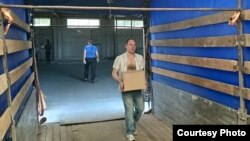 Удзельнік місіі Зьміцер Салаўёў разгружае гуманітарны груз