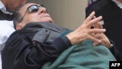 Египеттің бұрынғы президенті Хосни Мүбәрәкты сот залына зембілмен алып келді. Каир, 2 қаңтар 2011 жыл.