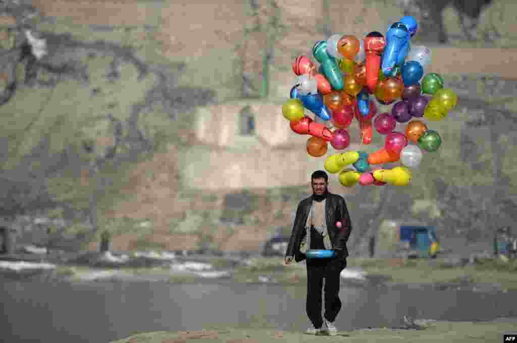 یک بادکنک فروش افغان در حال عبور از نزدیکی یک برکه در کابل