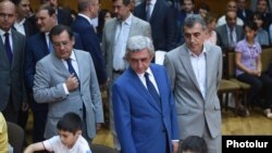Armenia -- Newly appointed Energy Minister Levon Yolian (far left) accompanies President Serzh Sarkisian (in the center) at a chess tournament in Yerevan (archive footage)