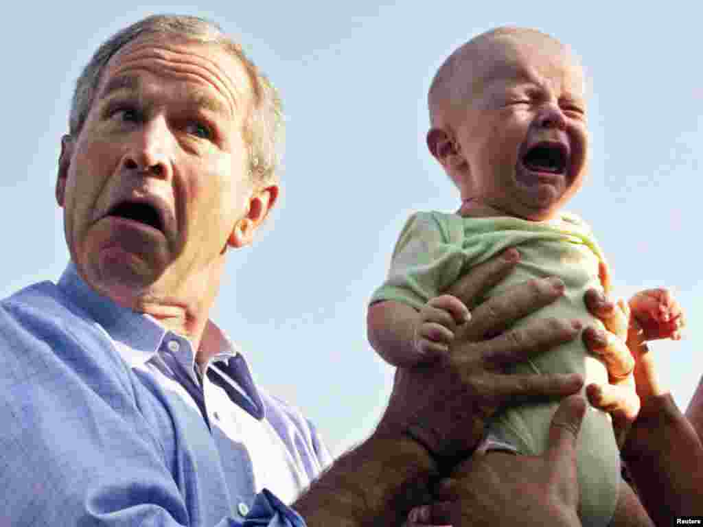 U.S. President George W. Bush hands back a crying baby that was handed to him from the crowd as he arrived for an outdoor dinner with German Chancellor Angela Merkel in Trinwillershagen, Germany, July 13, 2006. REUTERS/Jim Bourg