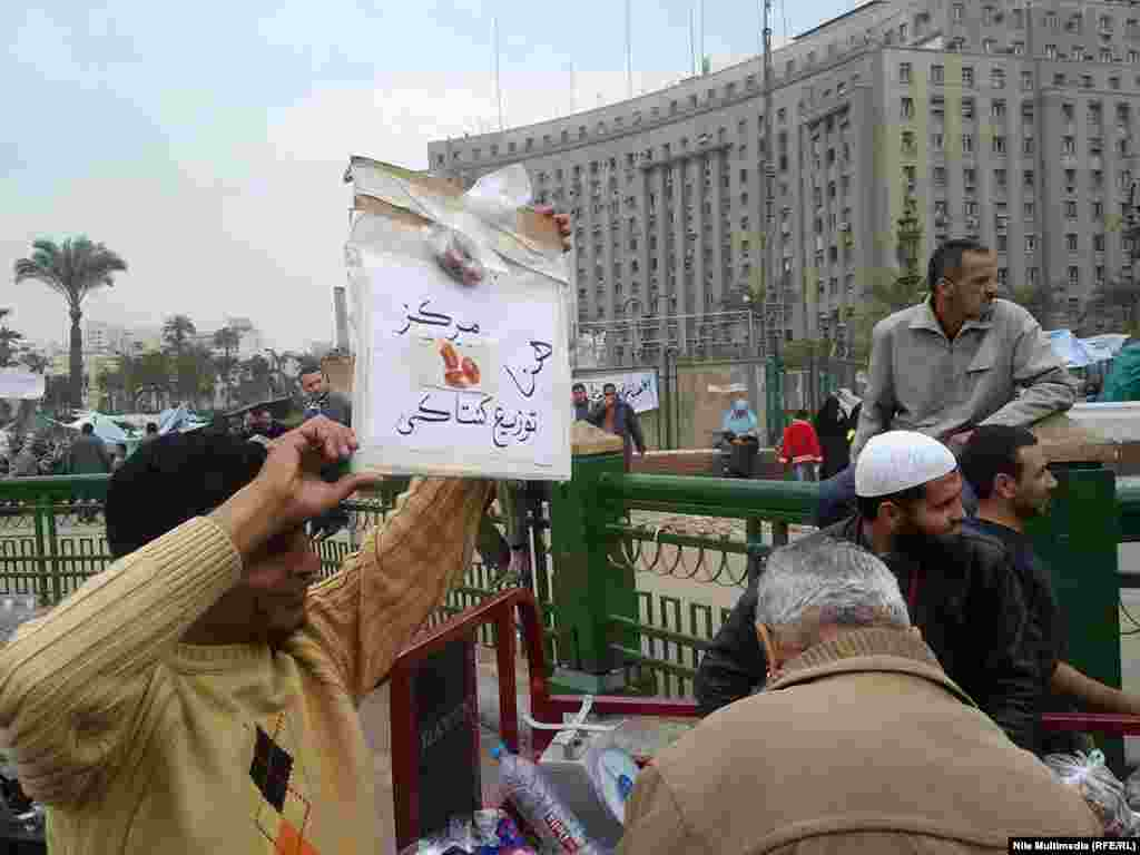 "This man is holding a sign reading, ""Here is the Kentucky distribution center,"" a reference to reports that pro-Mubarak supporters were being offered food from KFC to join counter-protests."