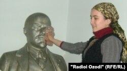 Як узви ҷавони Ҳизби коммунист нимпайкараи Владимир Ленин, доҳии коммунистонро аз чанг тоза мекунад